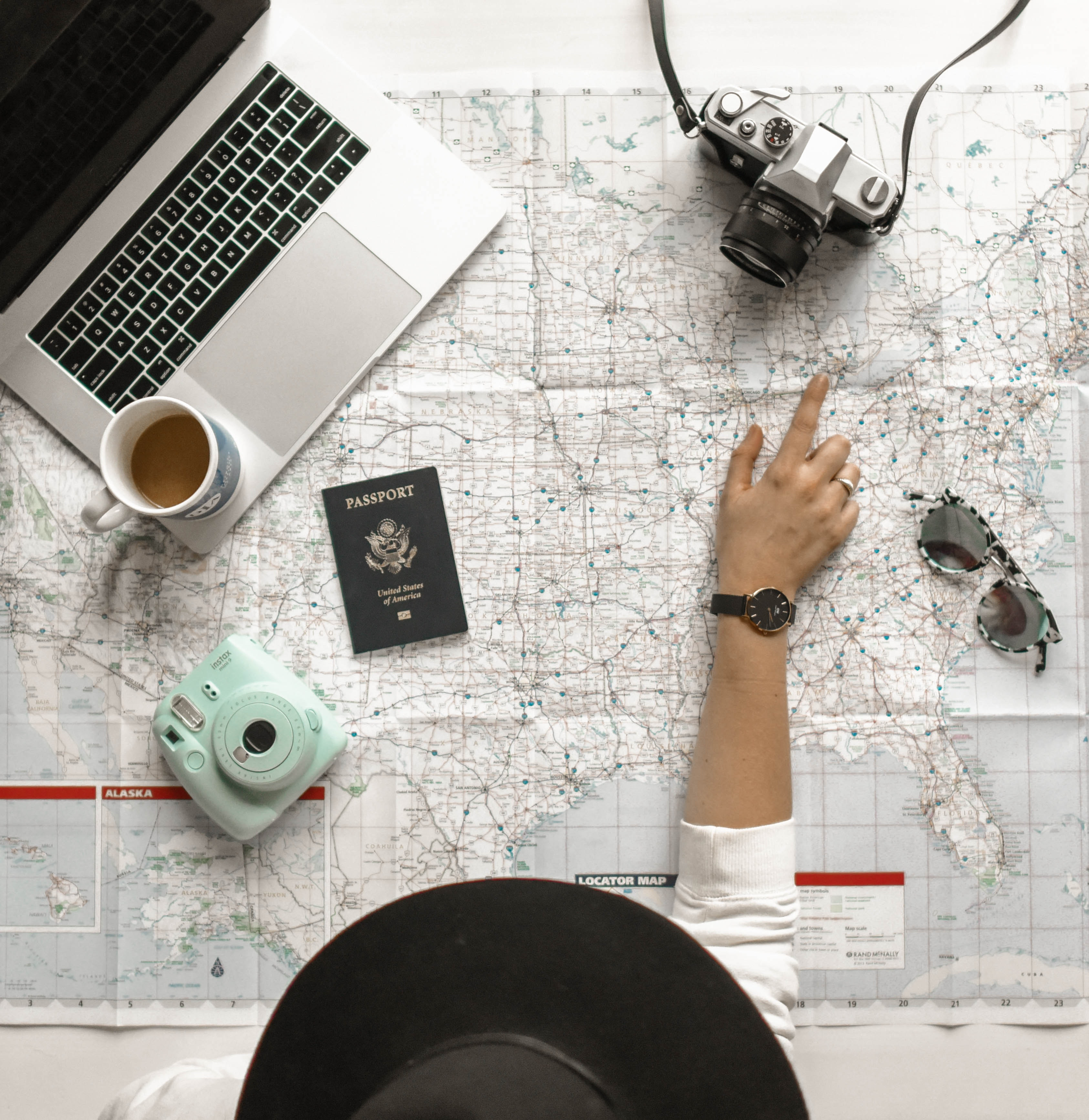 map spread out on the table with a camera, poloroid camera, passporat and sunglasses. Person pointing finer at a place on the map