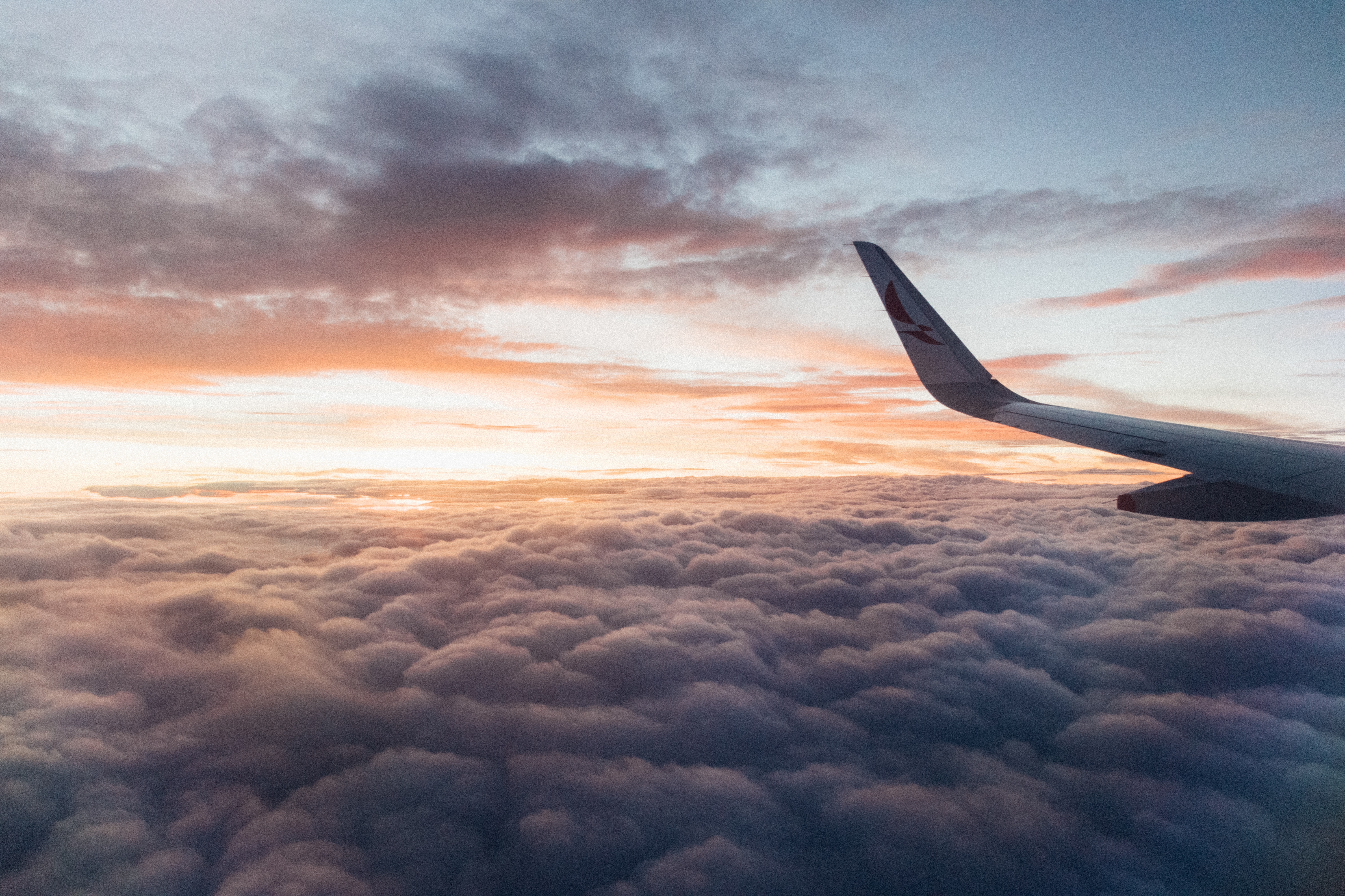 sunset at the cloud line with the wing of the airplane in the foreground